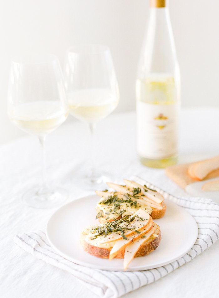 This combination of sweet pear, slightly salty crispy sage, mixed with the flavors of the brie will have your guests totally impressed, not to mention your taste buds! #recipe #crostini